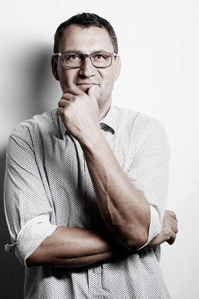 mediraum design Hagen Brockhaus mit Blick in die Kamera, leichtem Lächeln und lösungsorientierter Pose in Sepia-Optik