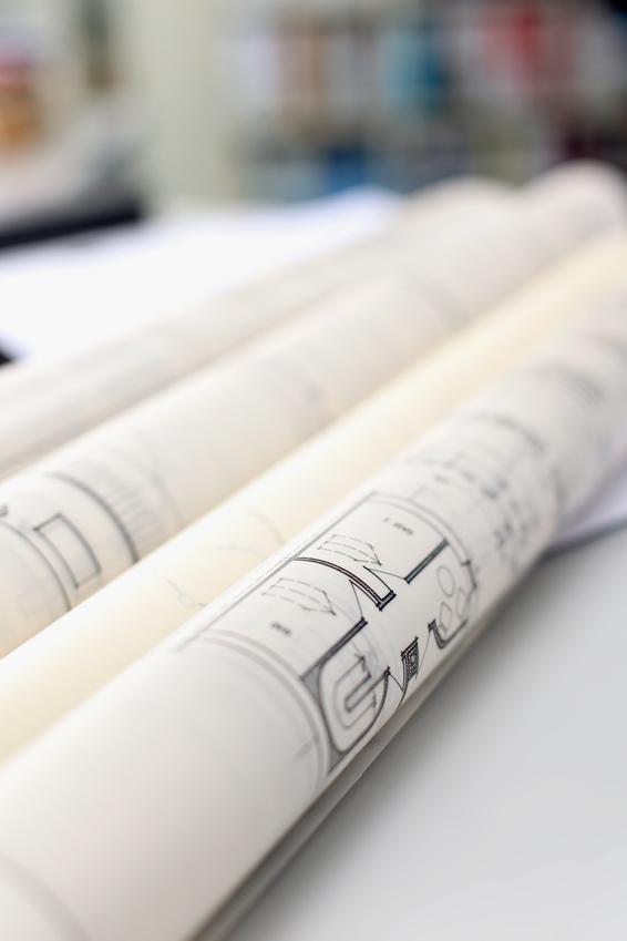 mediraum design Baupläne zusammengerollt auf einem Tisch liegend