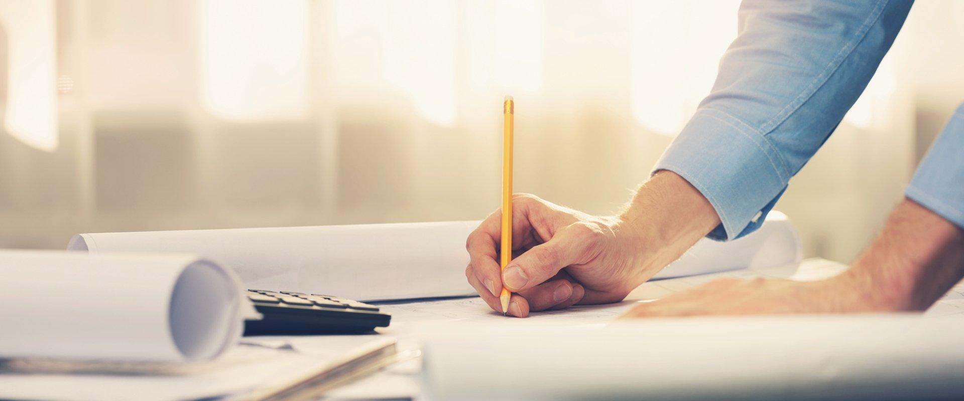 mediraum design Mann zeichnet mit Bleistift auf Bauplan in seitlicher Ansicht